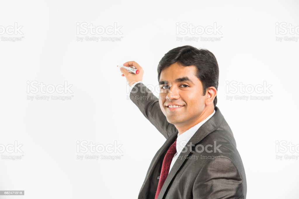 indian young businessman writing in the air with marker pen, isolated over white background royalty-free stock photo