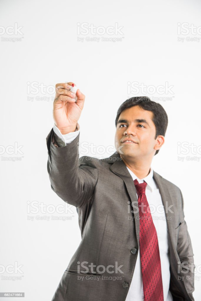indian young businessman writing in the air with marker pen, isolated over white background foto de stock libre de derechos