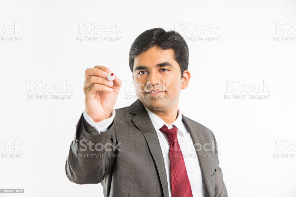 indian young businessman writing in the air with marker pen, isolated over white background Lizenzfreies stock-foto
