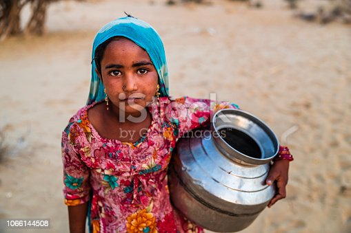 Indian young girl crossing sand dunes and carrying water from local well, Thar Desert, Rajasthan, India. Rajasthani women and children often walk long distances through the desert to bring back jugs of water that they carry on their heads.