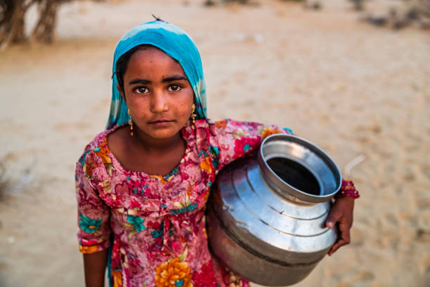 Indian young girl carrying water from well, desert village, India stock photo