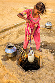 Indian young girl drawing water from a well. When she finish drawing water from the well, she will carry water on the head to the village. Rajasthani women and also children often walk long distances through the desert to bring back jugs of water that they carry on their heads . Thar Desert, Rajasthan. India.