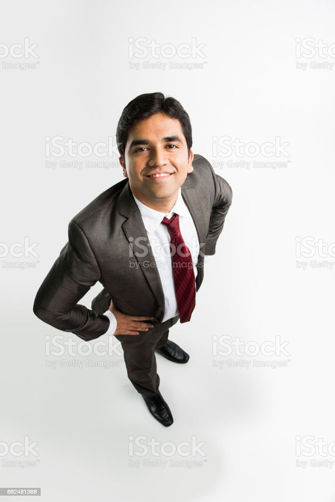 indian young & handsome businessman in clean shave and office wear standing, looking up / in the sky, a view from top also known as bird's eye view showing perspective, isolated over white background Стоковые фото Стоковая фотография