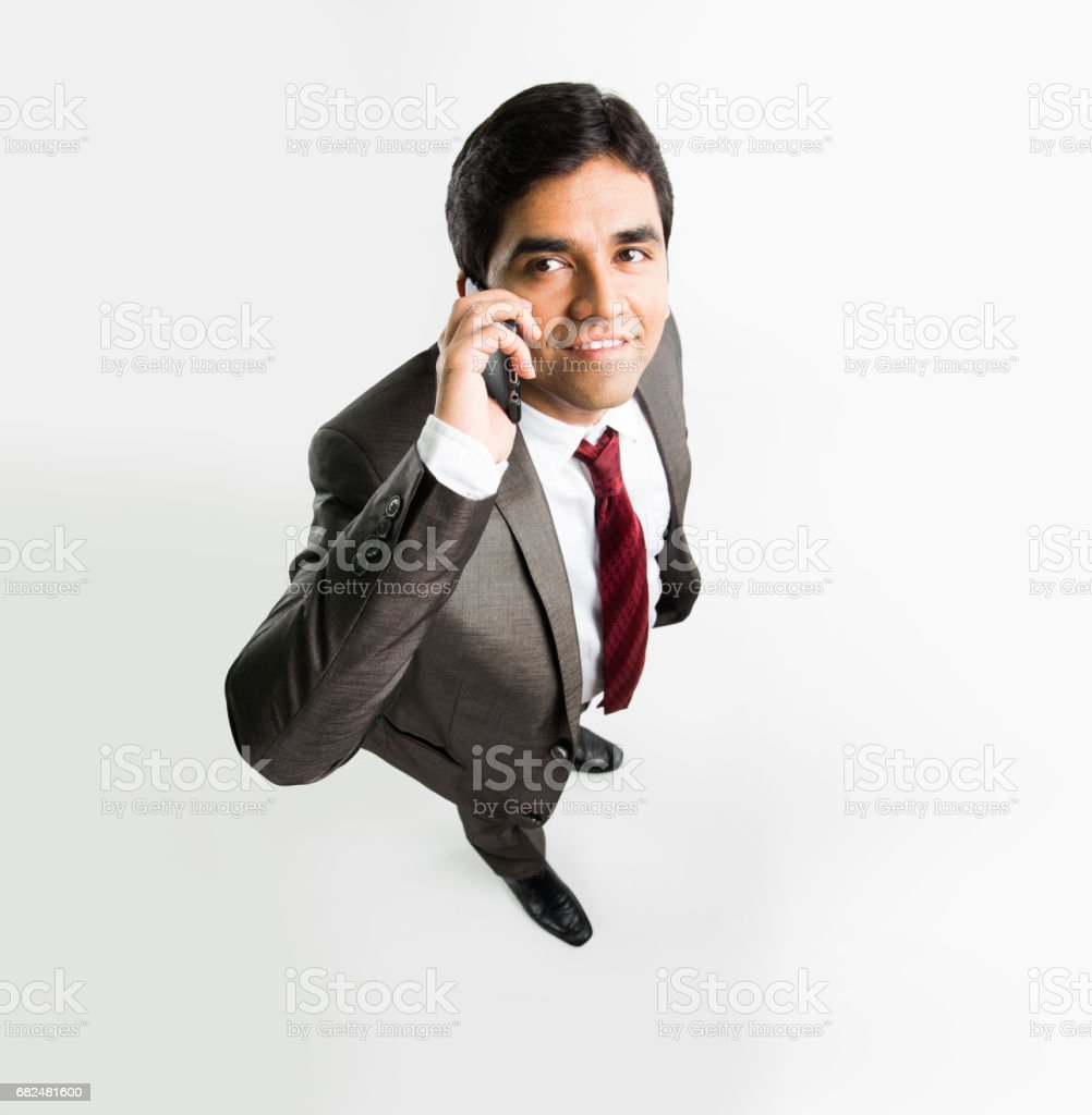 indian young & handsome businessman in clean shave and office wear standing, looking up / in the sky, a view from top also known as bird's eye view showing perspective, isolated over white background ロイヤリティフリーストックフォト