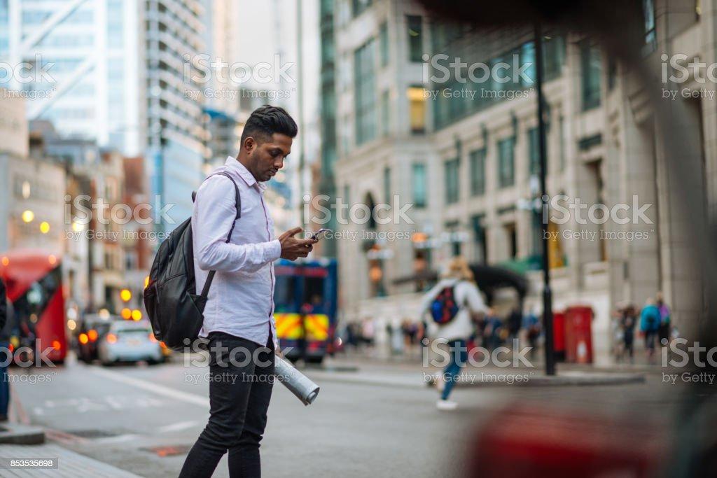 Indischen jungen Mann in London, Überquerung der viel befahrenen Straße beim Multitasking Lizenzfreies stock-foto
