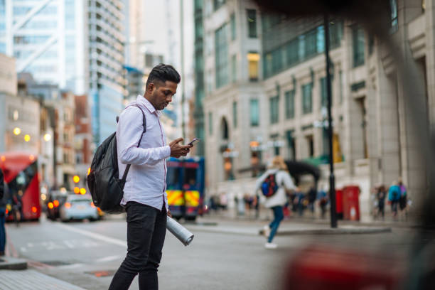 Indian young man in London, crossing the busy street while multi tasking Young man with Indian origins living in London. Indian or Pakistani man studies and works in London, United Kingdom. Young Hindu guy building his career in London migrant worker stock pictures, royalty-free photos & images