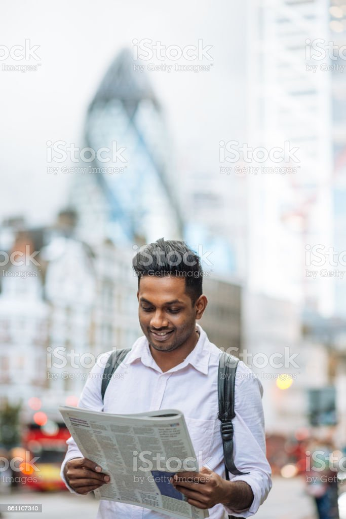 Indian young man reading newspaper and classified ads while waiting for the bus royalty-free stock photo