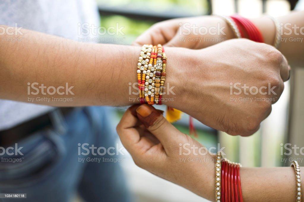 Indian young sister tying rakhi on brother's wrist, a tradition on Raksha Bandhan festival stock photo