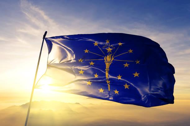 Indiana state of United States flag textile cloth fabric waving on the top sunrise mist fog stock photo