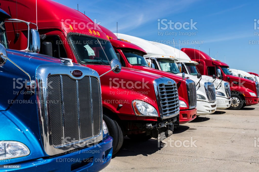 Indianapolis - Circa June 2017: Colorful Semi Tractor Trailer Trucks Lined up for Sale IX - foto stock