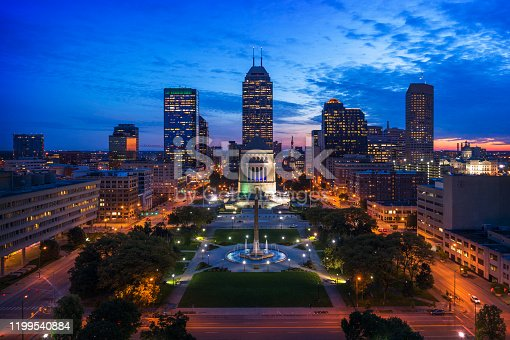 Downtown Indianapolis skyline aerial at dusk with Obelisk Square and the Indiana World War Memorial in the foreground.