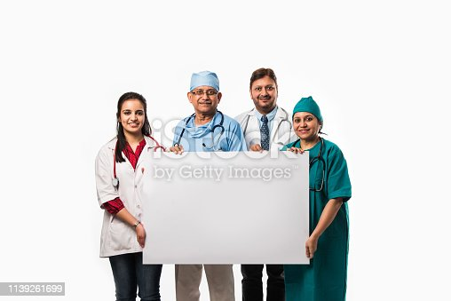 istock 4 indian/asian doctors holding white blank board with copy space, standing isolated over white background 1139261699