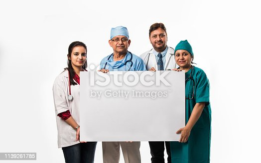 istock 4 indian/asian doctors holding white blank board with copy space, standing isolated over white background 1139261785