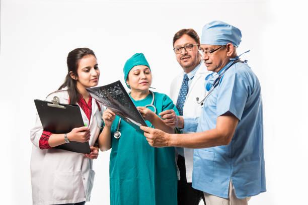 Indian/asiatische Ärzte suchen ein x-ray/MRT, isoliert über weißem Hintergrund. Selektive Fokussierung – Foto