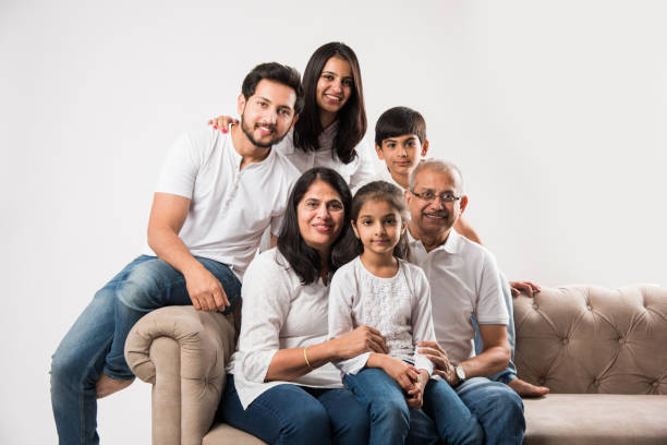 Indian/asian family sitting on sofa or couch over white background Indian/asian family sitting on sofa or couch over white background old mother son asian stock pictures, royalty-free photos & images