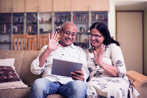 Indian/Asian Senior Paar Video-Chat auf Tablet/Computer während des Sitzes auf der Couch oder im Garten zu Hause, selektiver Fokus – Foto