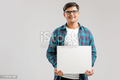 875677322istockphoto Indian/Asian Young Man showing blank signboard on White background 1175161487