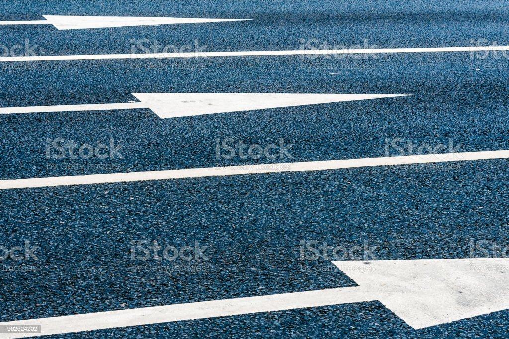 Setas indicativas em uma estrada de asfalto close-up - Foto de stock de Abstrato royalty-free