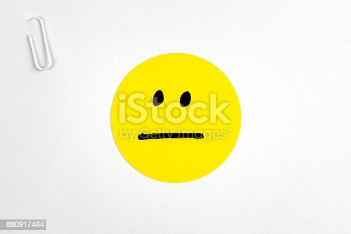 istock Indifferent neutral emoticon face over paper with paperclip. Paper yellow emoticon face on white background. 880917464