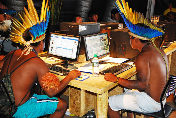 Indigenous amazonian Indians working with computers. stock photo