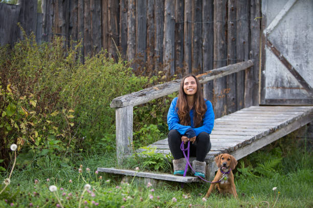 Indigenous Canadian woman sits with her dog stock photo