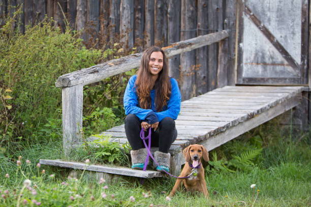 Indigenous Canadian woman sitting with her pet dog stock photo