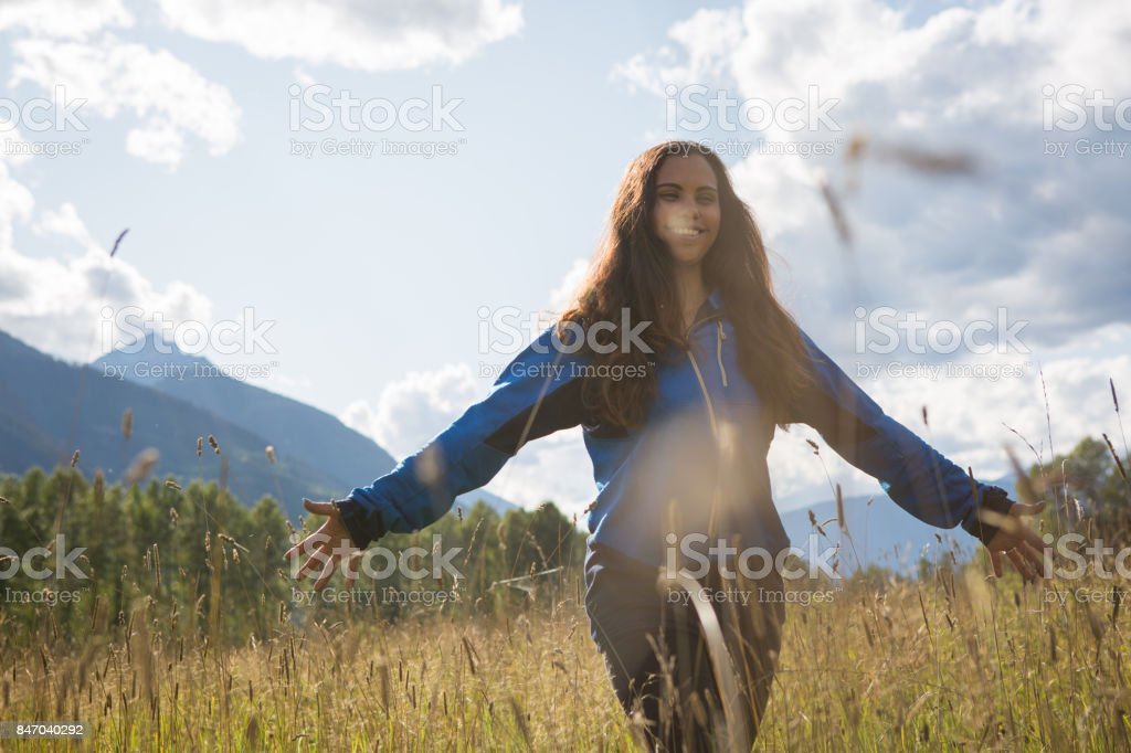 Indigenous Canadian woman walks through a lovely field stock photo