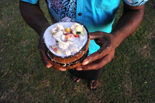indigenous fijian man serves fijian food, kokoda (raw fish salad) - fiji stock photos and pictures