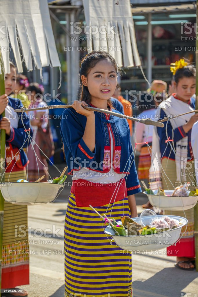 Indigenous girl holding counterpoise with 2 enameled basin of food in parade stock photo