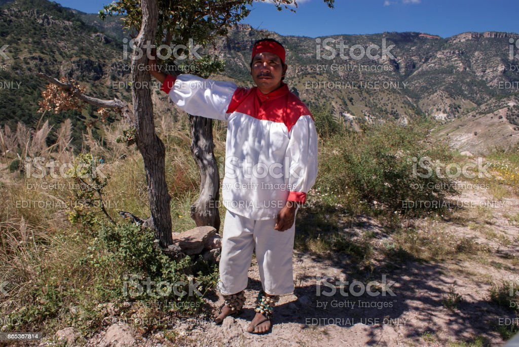 Indigenous Tarahumara man takes rest under the shade of the tree, wears traditional tribal outfit stock photo
