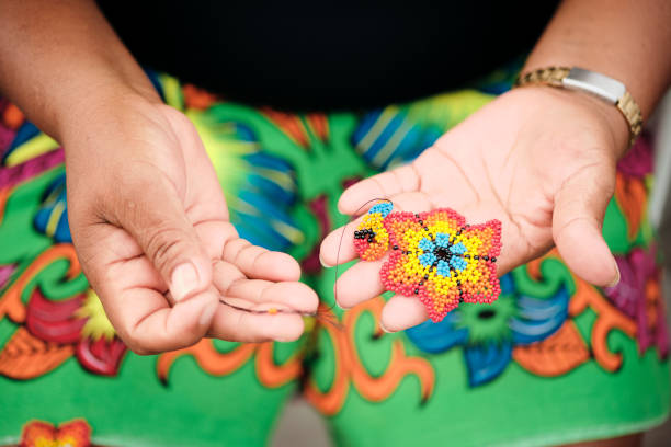 Indigenous Woman Beading Flower Coaster At Market Stall For Tourists stock photo