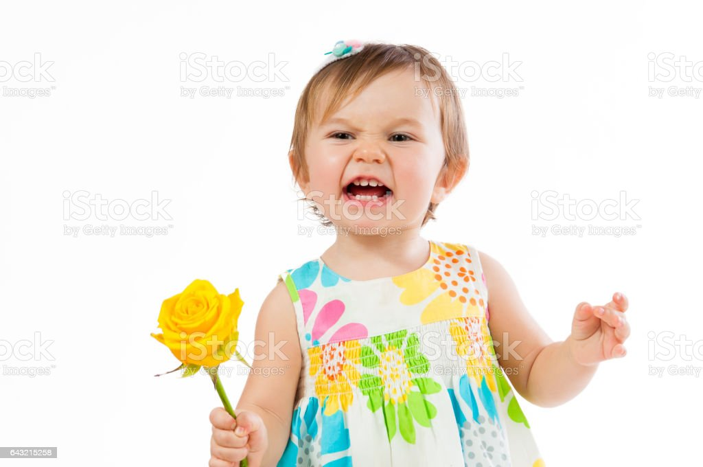 Indignant little girl with a yellow rose, romantic gift stock photo