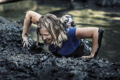 Individual beautiful blonde woman having sporty fun at a public mud run obstacle course