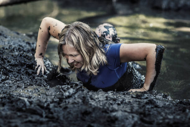 Individual beautiful blonde woman having sporty fun at a public mud run obstacle course Individual beautiful blonde woman having sporty fun at a public mud run obstacle course obstacle course stock pictures, royalty-free photos & images