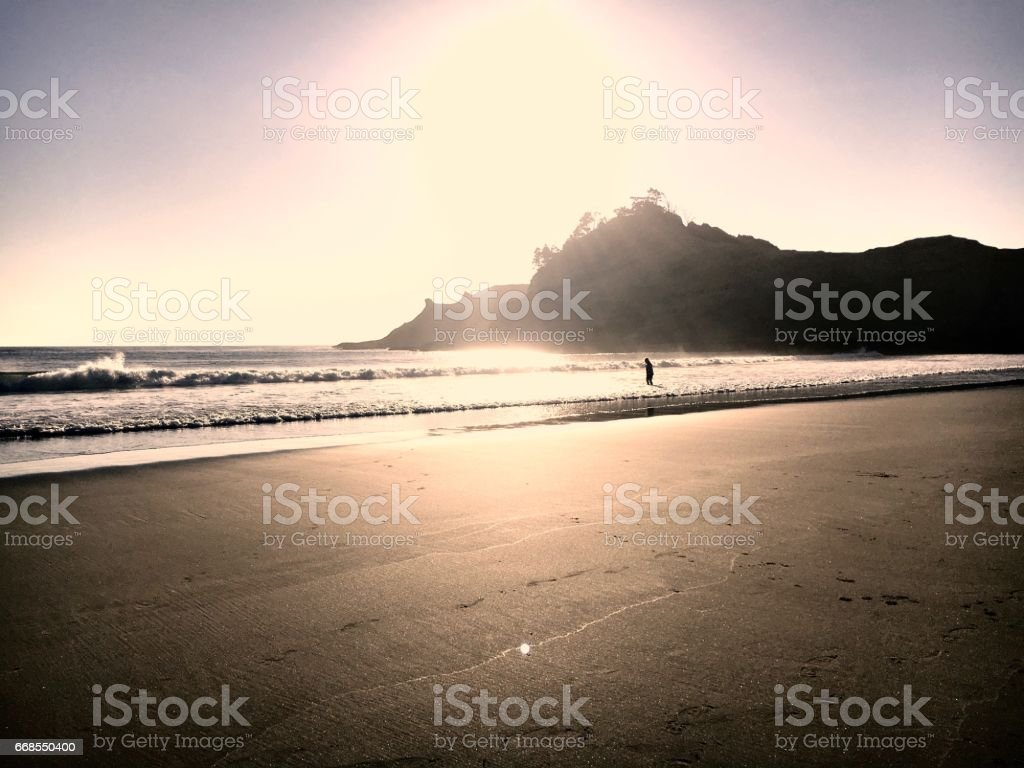 Individual Entering the Ocean at Sunset stock photo