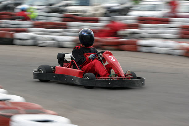 Individual in protective gear riding a go cart stock photo