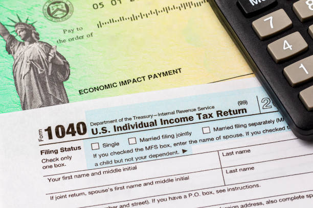 1040 individual income tax return form and economic impact payment or stimulus check. Concept of filing taxes, taxable income and tax information. background, no people stimulus check stock pictures, royalty-free photos & images