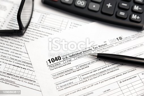 U.S. Individual income tax return. Tax form 1040 with eyeglasses and pen