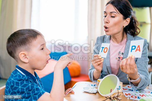 istock Individual Primary Education. Teacher and Pupil at Reading Lesson 1015878602