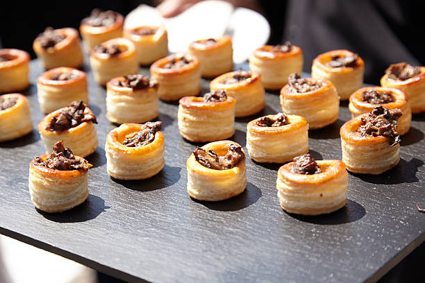 individual puff pastry wedding appetizers on a slate tray - 누벨퀴진 뉴스 사진 이미지