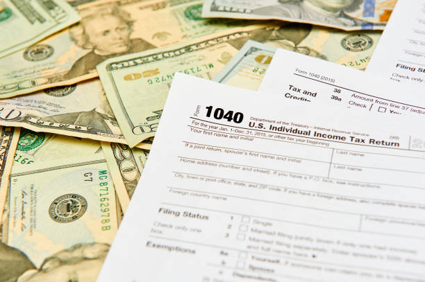 1040 Individual Tax Return form on top of a table full of paper money. stock photo