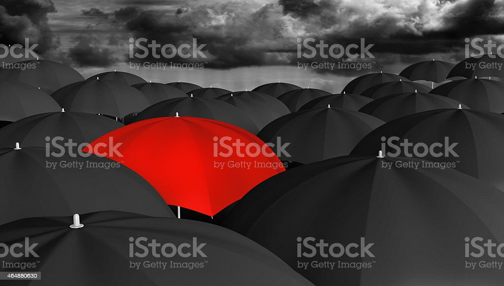 Individuality concept of a red umbrella among many black ones stock photo