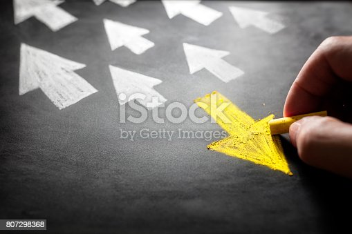 istock Individuality going a different direction chalk arrow on blackboard 807298368