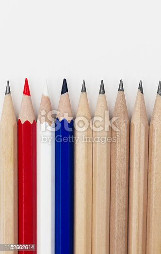 Red,white and blue pencils representing a flag in a row of normal brown pencils.