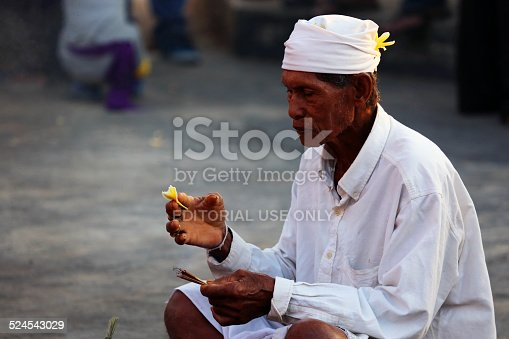 Uluwatu, Indonesia - August 22, 2014: A priest lights the altar and gives blessing to the site before the Kecak ceremony. Also known as the Ramayana Monkey Chant, it is a retelling of a great battle from the Ramayana of Hindu lore.