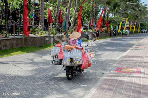 Indonesia Kuta Sept 20 2019, Woman with lots of stuff on scooter in Bali colors