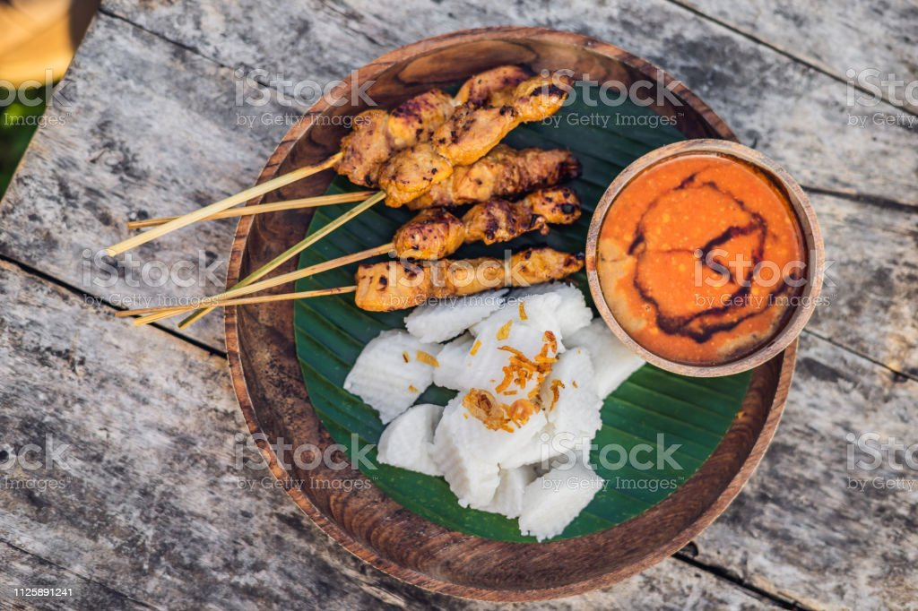 Indonesian chicken satay or Sate Ayam served with lontong, soy sauce and peanut sauce lifestyle food stock photo