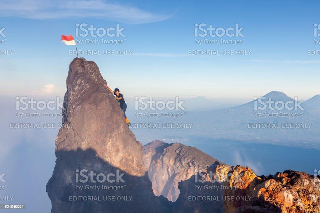 Indonesian climber climbing to highest peak of Merapi volcano at Java island, Indonesia. stock photo