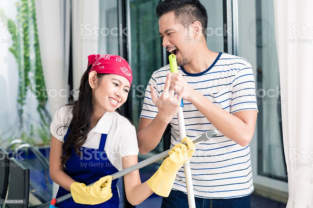 Indonesian couple having fun cleaning the home stock photo