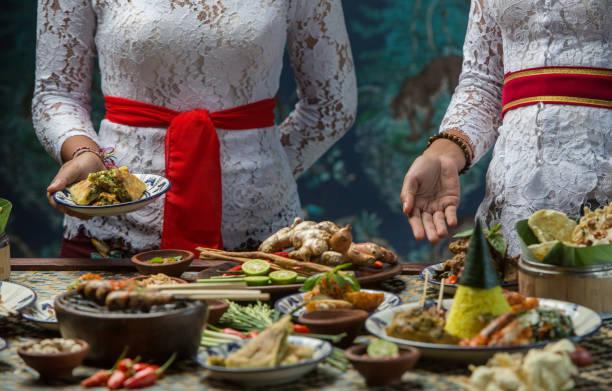indonesian cuisine - many traditional balinese dishes on the table. waitress is serving food - kultura indonezyjska zdjęcia i obrazy z banku zdjęć